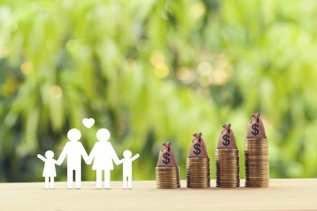 Планирование безопасного будущего и финансового положения и концепция снижения налогов: члены семьи, американские денежные мешки на рядах поднимающихся монет на столе. изображает сбережения для роста благосостояния и доходов
