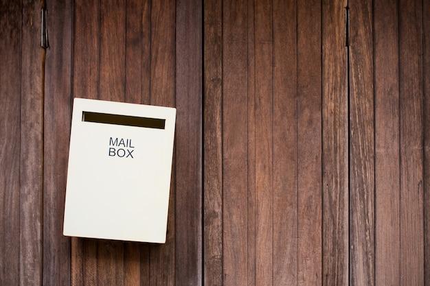 木製の背景上のメールボックス