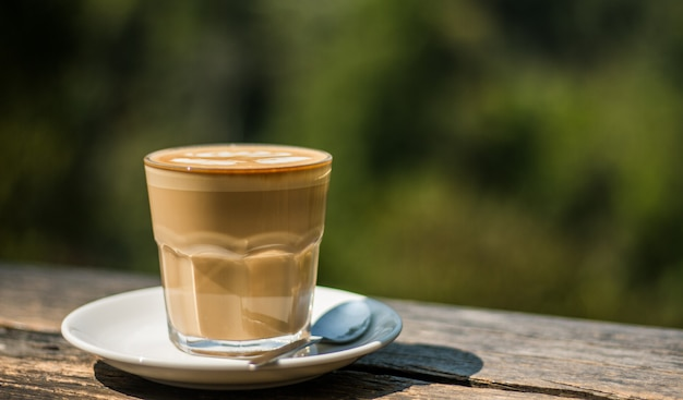 Чашка кофе латте на деревянной барной стойке в кофейне