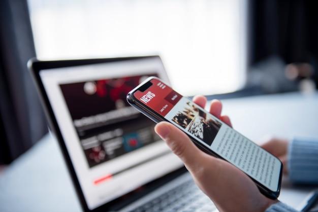 スマートフォンとラップトップのオンラインニュース。モックアップのウェブサイト。自宅で携帯電話の画面アプリケーションでニュースや記事を読む女性。インターネット上の新聞とポータル。