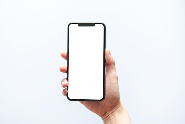 スマートフォンのモックアップ。黒い電話の白い画面を持っている手を閉じます。白い背景で隔離されました。携帯電話フレームレスデザインコンセプト。