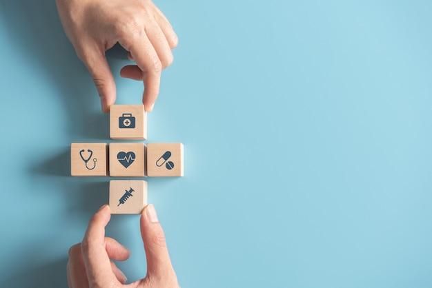 Руки, устраивая деревянный куб с медицинским символом на пастельных синих