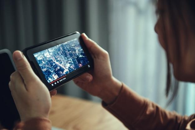 Поток онлайн фильмов со смартфона. женщина смотрит фильм на мобильном телефоне с мнимой видео плеер услуг.