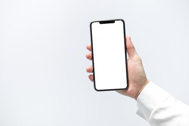 スマートフォンのモックアップ。黒い電話白い画面を持っている実業家の手