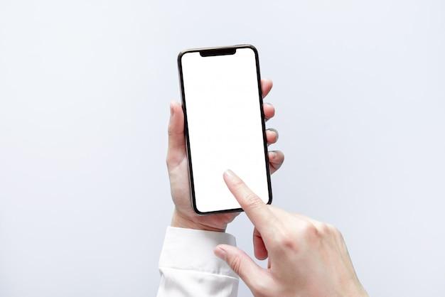 スマートフォンのモックアップ。黒い電話白い画面を使用して実業家の手
