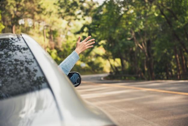Рука с поднятой рукой, расслабляющаяся и наслаждающаяся поездкой