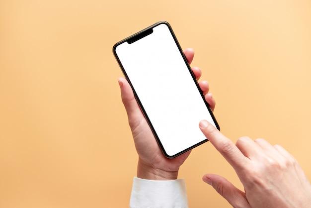 Закройте вверх руки, держащей черный смартфон белый экран