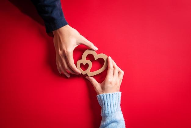 愛の概念、赤の手に心と恋のカップル。バレンタイン・デー