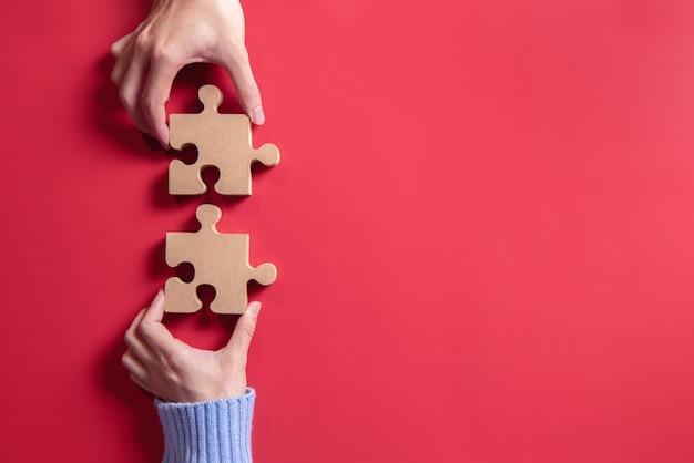 ジグソーパズルを保持している手。チームワークの概念成功の構築。