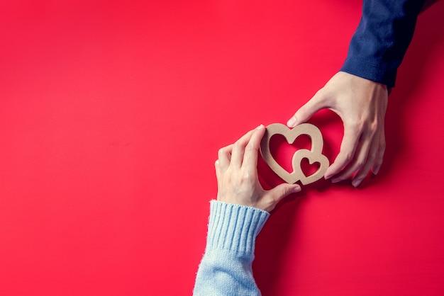 Любовь концепции, влюбленная пара с сердцем на руках на красном