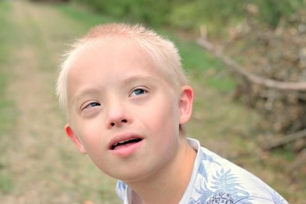 屋外の肖像画のためのダウン症候群の少年ポーズ