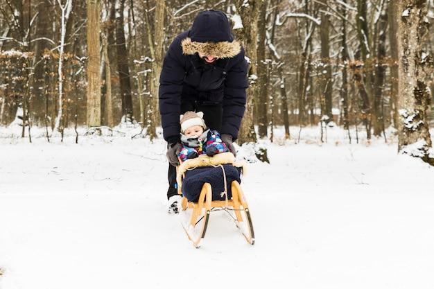 Детские санки на снегу в лесу