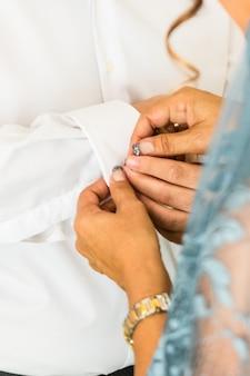 彼が彼の結婚式の日に服を着るようにカフスボタンを身に着けている新郎。新郎のスーツ