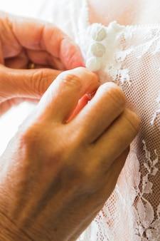 花嫁介添人花嫁のコルセットを締め、彼女のドレスを取得
