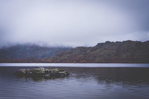 低い雲と山々の間の湖