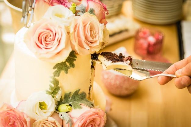 結婚式のカップルが彼らの結婚式の日にウエディングケーキを切る