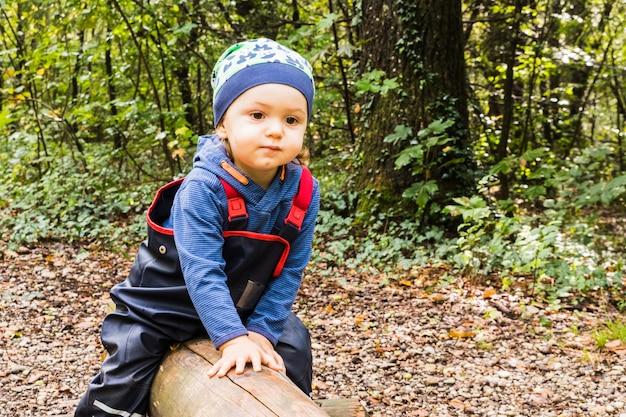 秋の森の小道で遊ぶ赤ちゃん