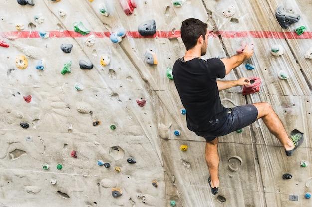 男は室内の人工壁にロッククライミングを練習します。アクティブなライフスタイルとボルダリングの概念