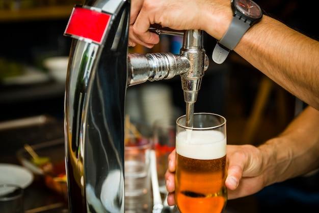 バーテンダーはタップから新鮮な冷たいビールを注ぐ