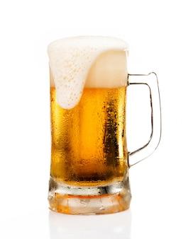 白い背景で隔離のガラスの上の泡の泡とビールのジョッキ