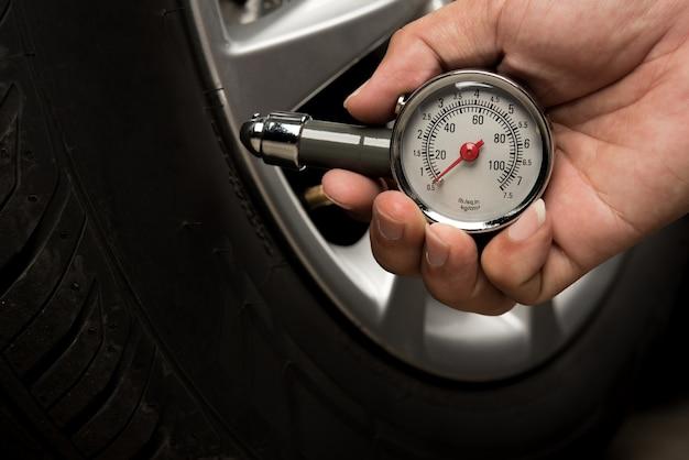 Рука человека, держащего калибровочное измерительное давление, проверяющее шину автомобильного транспорта