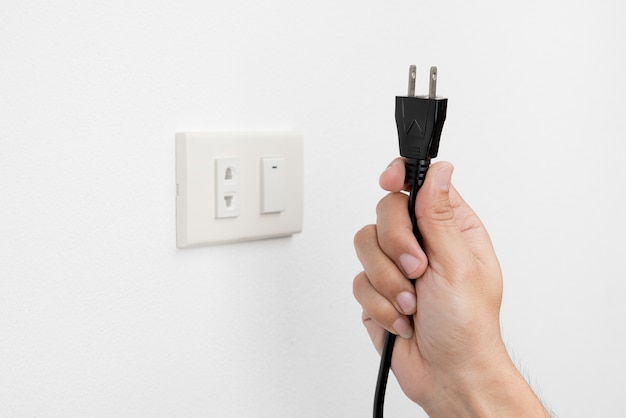 壁の白い背景の安全コンセプトの電気コンセントプラグを抜く男の手