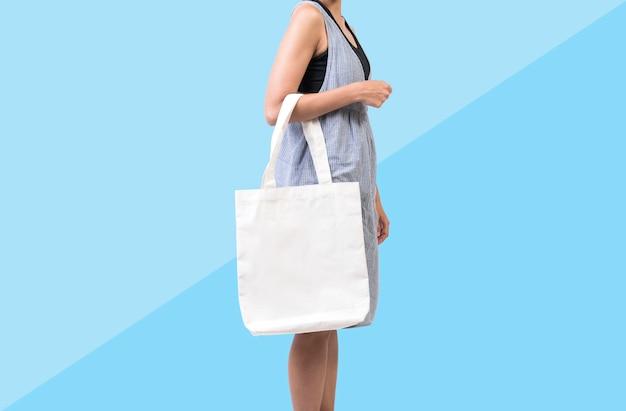 Девушка держит мешок холст ткани для макета пустой шаблон, изолированных на синем фоне.