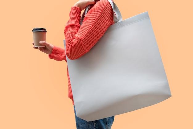 Девушка держит мешок холст ткани для макета пустой шаблон, изолированных на цвет фона.