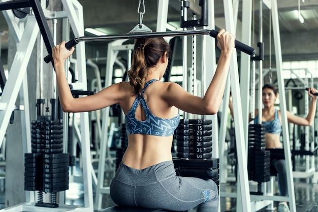 アジアの若い女性がジムで運動します。健康的なライフスタイルとトレーニングの動機づけの概念。