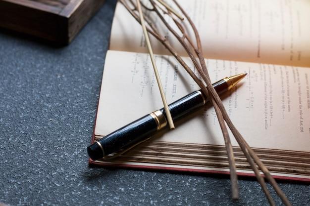 Черная ручка, сухоцветы и книга на темном фоне