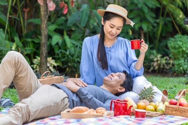 シニアアジアカップルが庭でコーヒーとピクニックを飲みます。