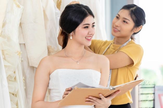 テーラーアシスタントとショップでドレスを選択する美しいアジアの女性。