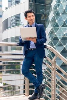 ハンサムなアジアビジネスマネージャー男立って、屋外の街でノートパソコンでの作業。