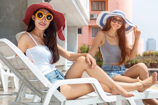 Молодая азиатская женщина в солнечных очках ослабляя и сидя на шезлонге.