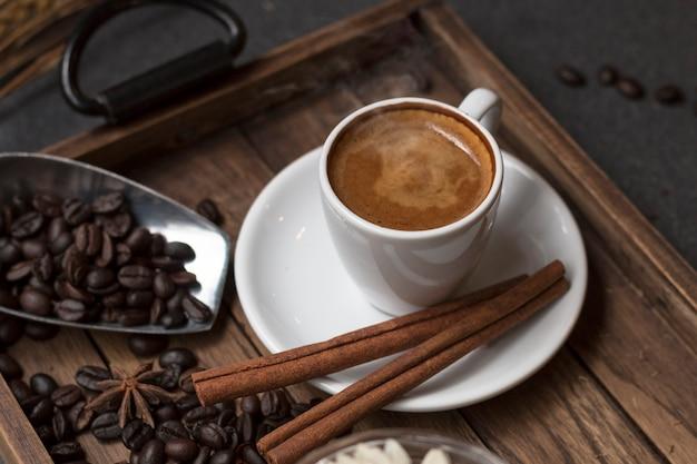 木製トレイのエスプレッソカップ、コーヒー豆、シナモン、ドライフラワーの瓶。