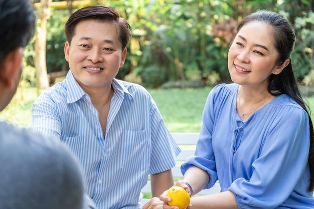 Старшие азиатские пары консультируя и встречая финансового советника.