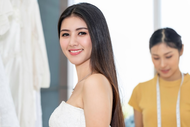 若い女性アジアの笑顔とお店でウェディングドレスを試着します。