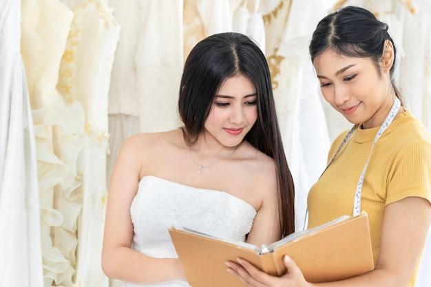 かなりアジアの女性がテーラーアシスタントの店でドレスを選ぶ。