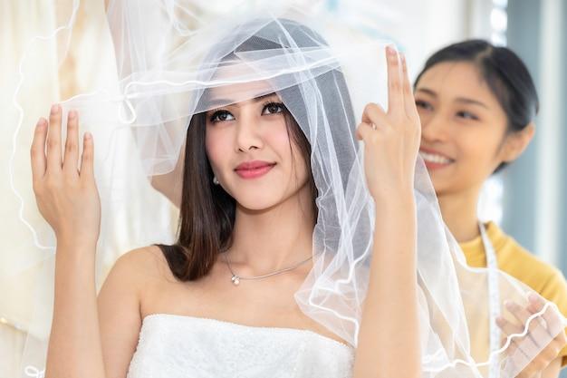 笑顔のアジアの女性が仕立て屋で店のウェディングドレスで測定します。