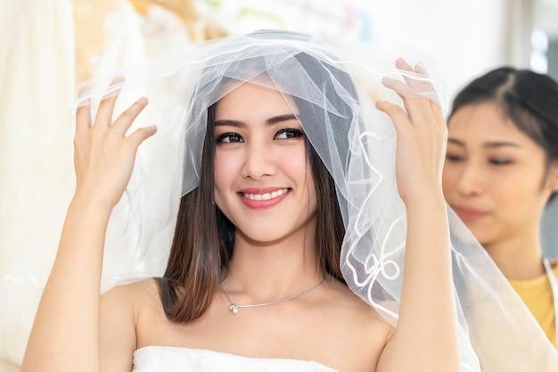 若いアジアの女性が仕立て屋で店のウェディングドレスで測定します。