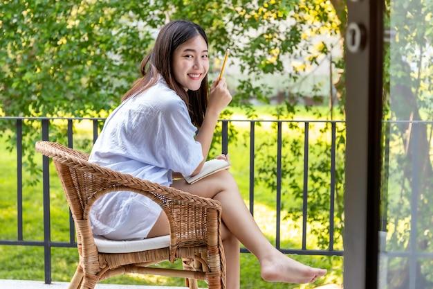 バルコニーでノートを書く若い女性。