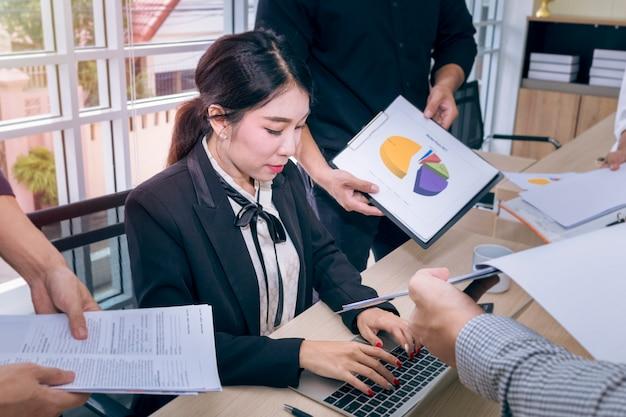若い実業家がドキュメントに署名し、オフィスでのビジネスチームワークとの出会い。
