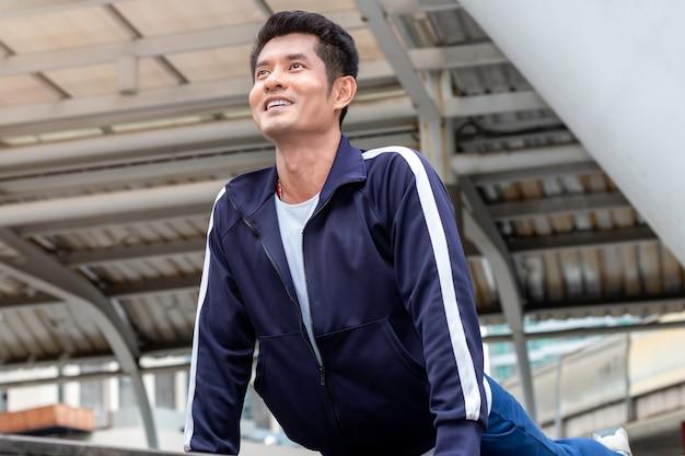 ハンサムなアジアのスポーツマンが体を伸ばして、路上で演習を行います。