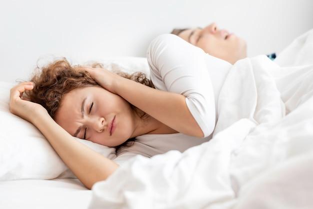 Кавказская пара в пижамах храпит и плохо спит на спальне. она блокирует уши руками.
