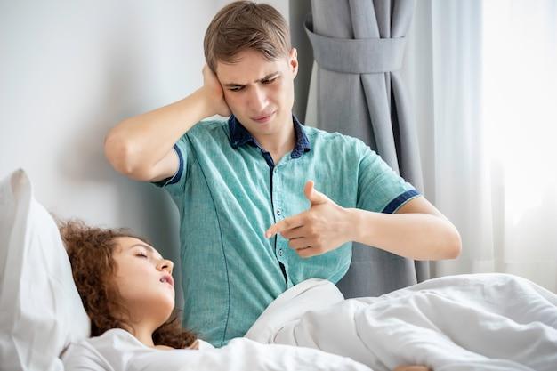 Кавказская пара в пижамах храпит и плохо спит на спальне. его блокируют уши руками.