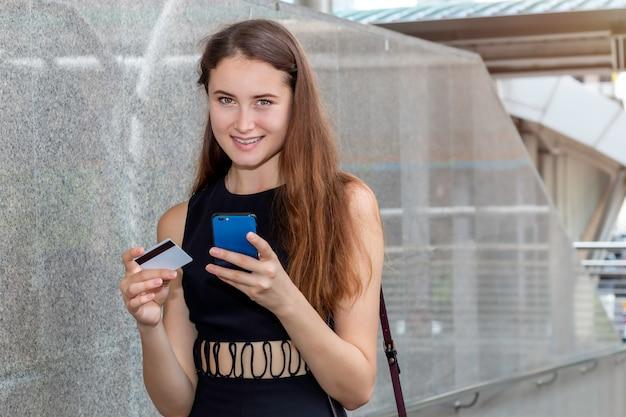 クレジットカードとスマートフォンアプリケーションをオンラインで購入するスマートな白人女性。