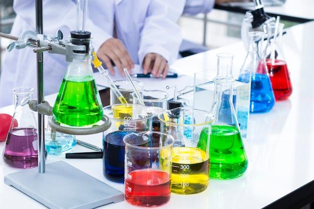実験室で顕微鏡の近くの試験管とビーカーの中の色の水。