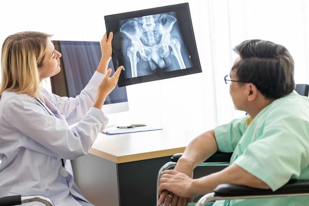 Медицинские работники кавказская женщина рентгеновского и разговор с пожилым человеком азии пациента.