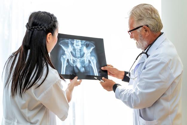 Медицинские работники кавказский старший мужчина, проведение рентгеновских и разговор о пациенте с молодой доктор женщиной.