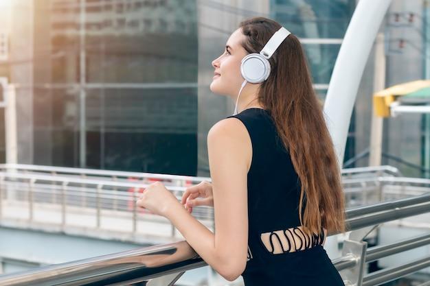 Музыка красивой кавказской женщины слушая с наушниками в городе.